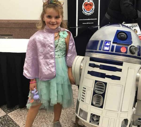 little girl cosplaying with R2D2